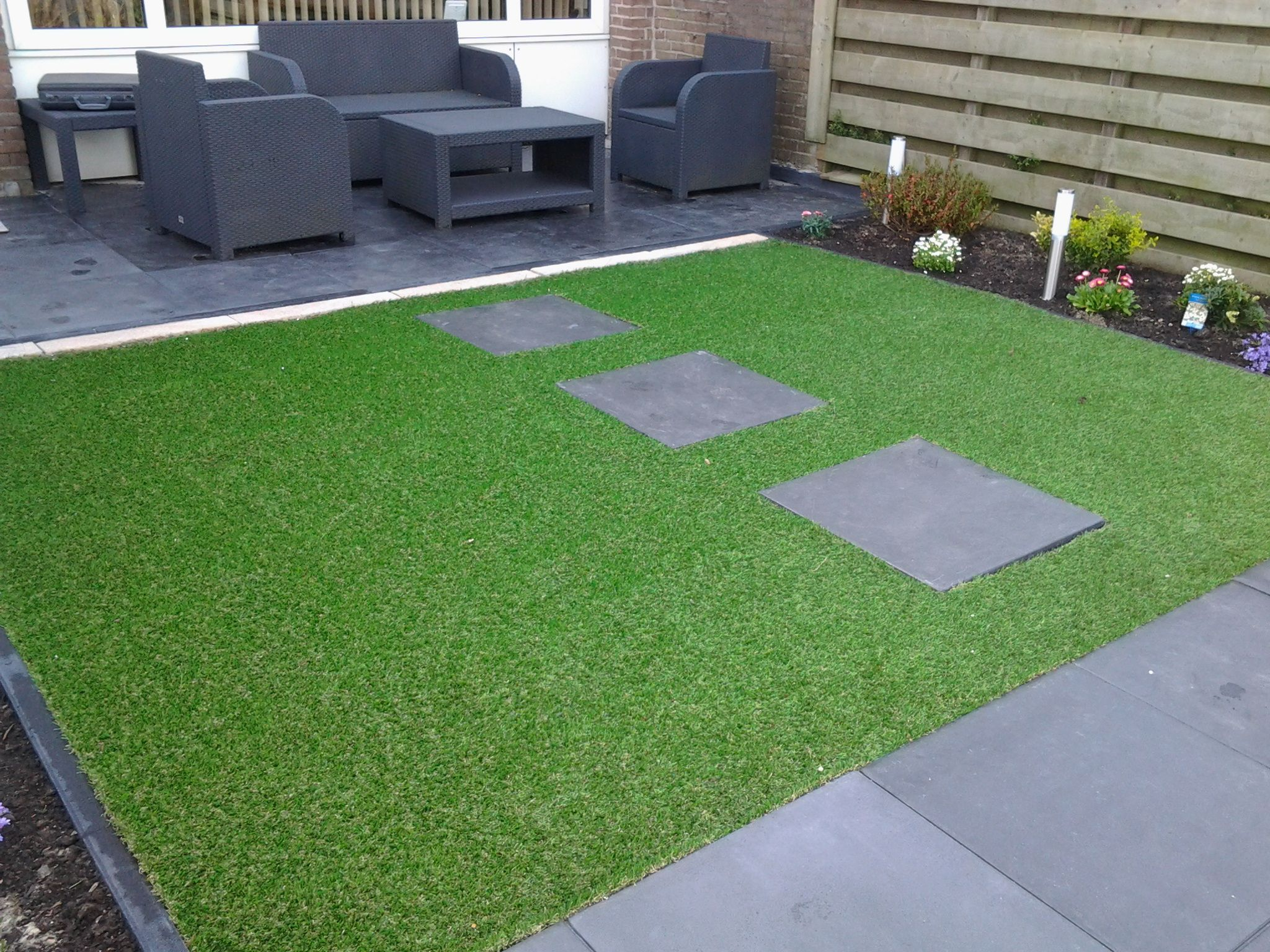 Artificial turf next to pavers For the Home