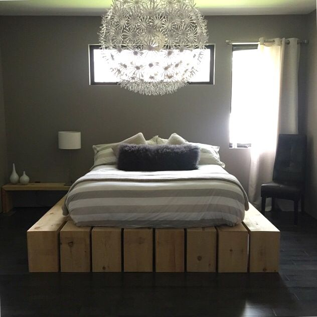 Homemade wood frame bed with a ikea ps maskros lamp in a grey and beige masterbedroom