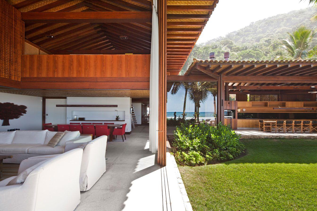 """Esta casa """"pé na areia"""" no litoral paulista foi implantada em forma de U, criando um jardim interno e direcionando a vista para a praia."""