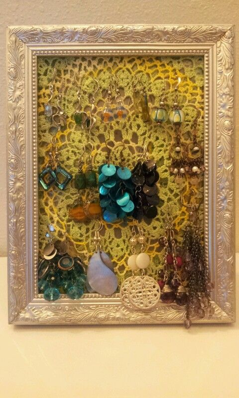 ©2013 Amber Hartje - designeroni.com     I made my own $5 earring holder!      Super easy: 1. Go to your local Savers, thrift store, or yard sale. 2. Buy frame & a lace doiley (my frame was $2.99 & the doiley was $1.99 at Savers) 3. Place lace over the glass from the picture frame & tuck glass & lace back into frame. 4. Arrange earrings on lace & you have a stylish way to display your earrings.   (Tip: Try to buy a lace doiley that is close to the same size as the picture frame glass.)