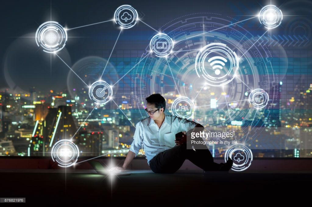 ストックフォト : technology and innovation concept, Asian businessman sitting and using the laptop showing Wireless communication connecting of smart city Internet of Things Technology over the cityscape background