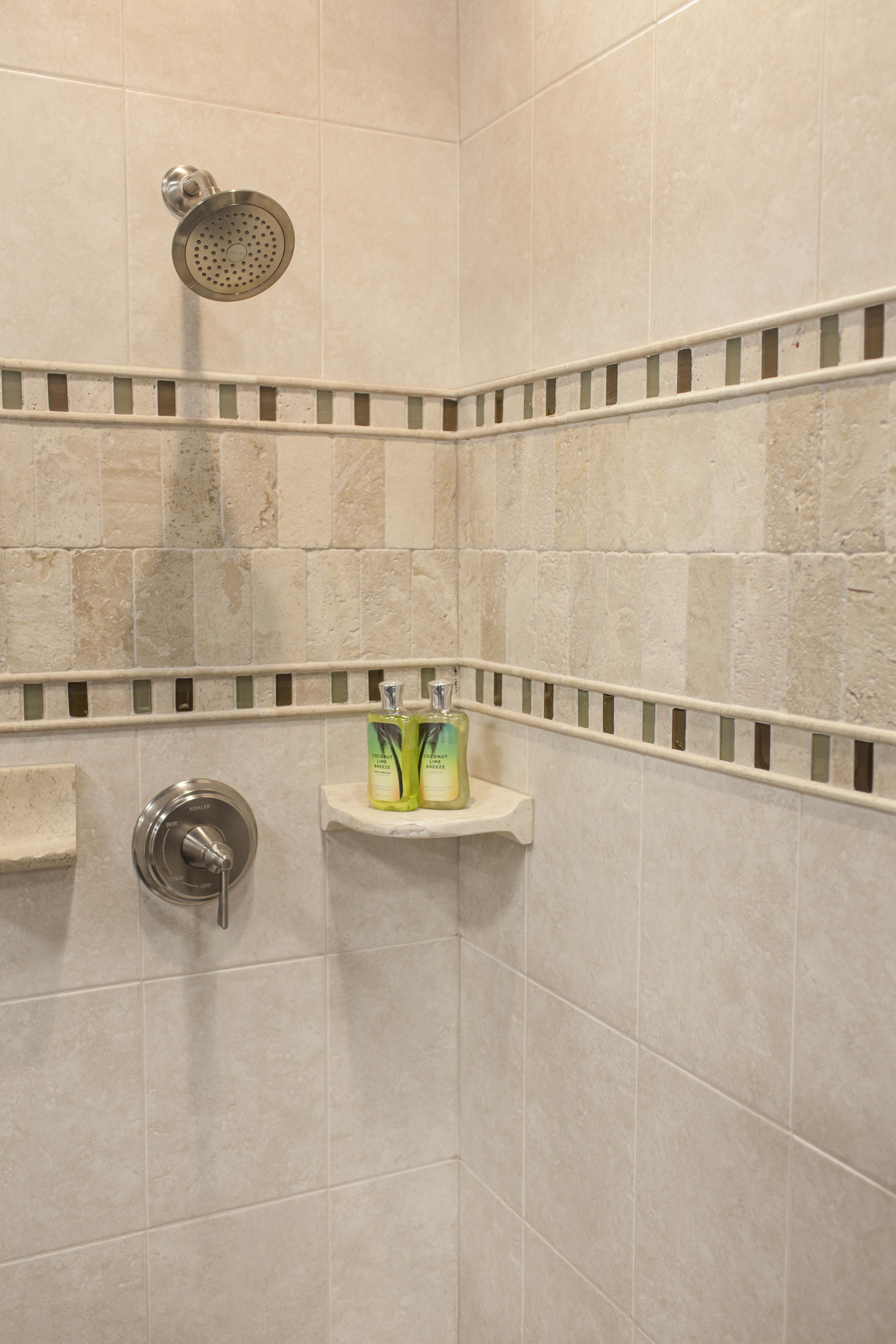 Travertine And Glass Shower Accents Make Ordinary Ceramic Tile