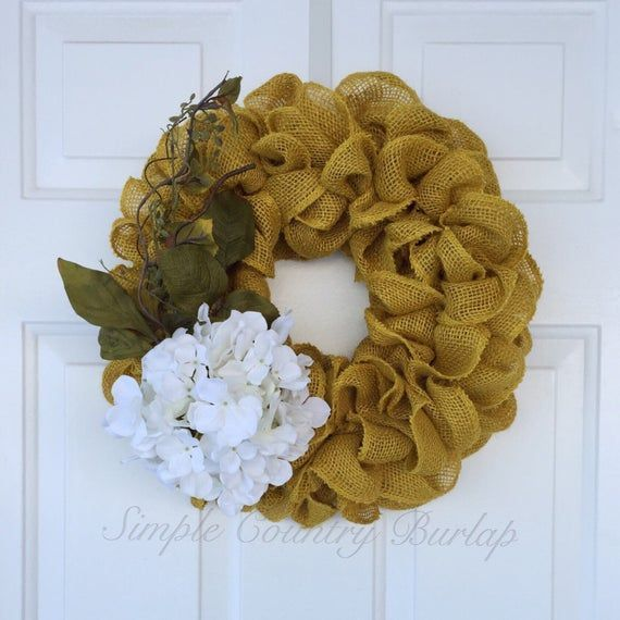 Yellow burlap wreath accented wtih a white hydrangea and green leaves Yellow burlap wreath accented wtih a white hydrangea and green leaves,