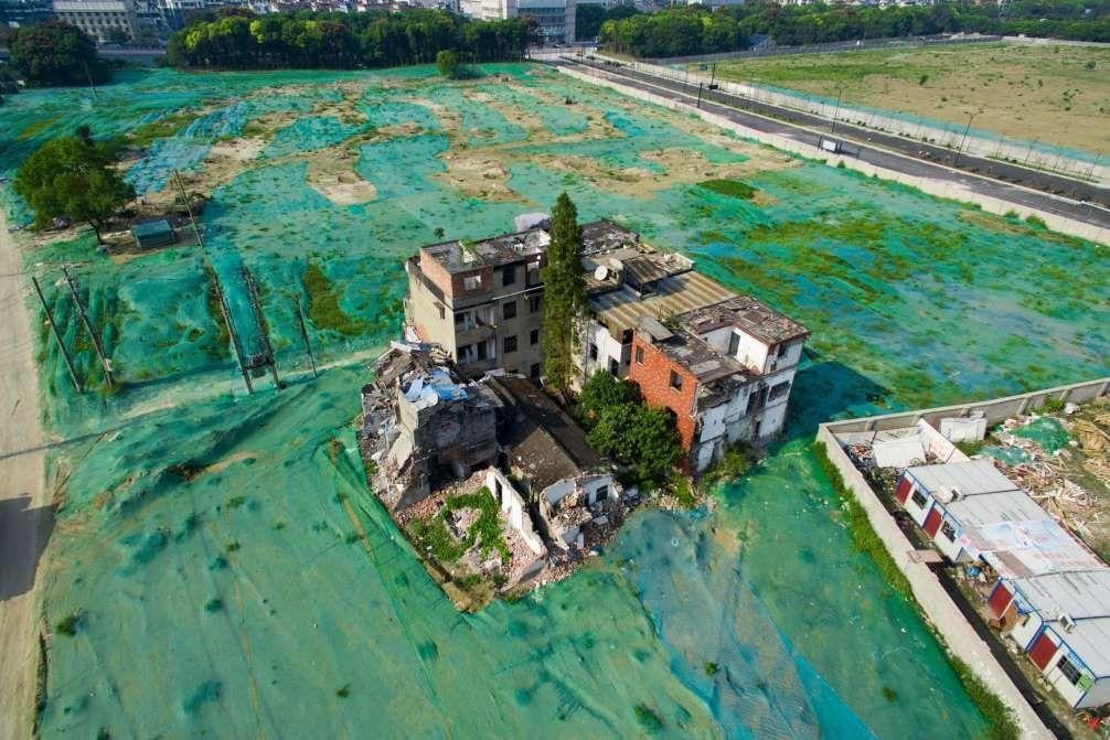 A nail house is seen in the middle of an area covered by a dust screen on Sept. 26.Hangzhou, China  Die Bewohner des Hauses weigern sich ihr Zuhause zu verlassen, um Platz für Bauarbeiten zu machen. Nun leben sie inmitten eines Geländes, das komplett mit einer grünen Staubwand abgedeckt ist.