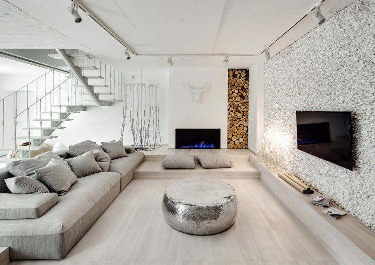 Intérieur blanc du salon de design contemporain avec rangement pour le bois et mur en galets