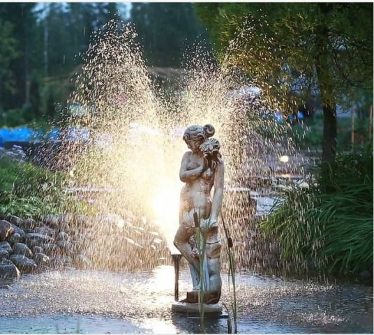 Valoa ja vettä patsaan ympärillä.