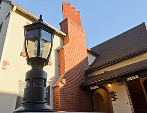 New patio lights brighten a patio with a table for two. Notice the triple flue chimney that was custom built to represent the three units on the property.