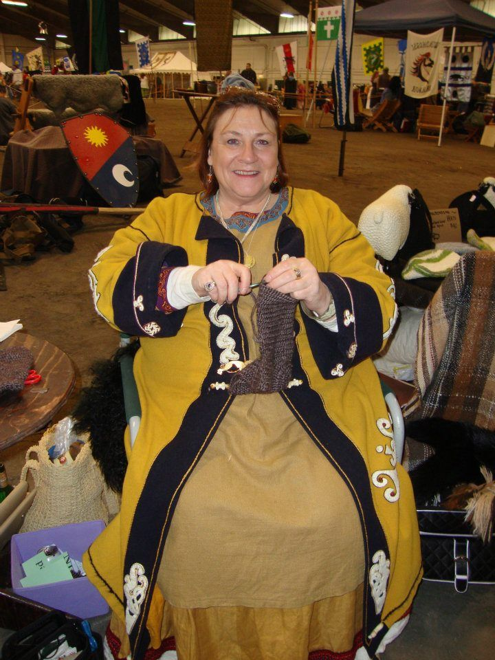 Interesting designs on the coat (likely not period, however).  Note the turned-up cuffs.  This one might not be intended to be Viking--the shorter gown underneath appears to have a neckline and not a straight edge like an apron-dress, but it's a similar fashion and appears to be Early Period in intent, so I've included it.