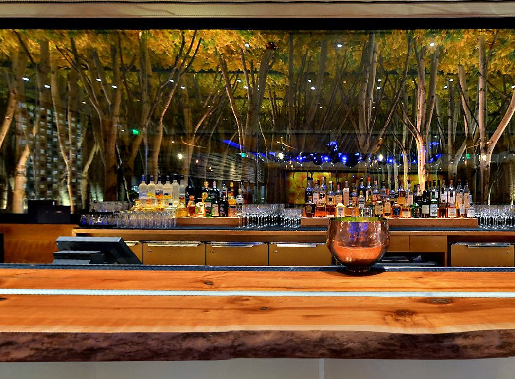 """Bar at American Fish, Las Vegas. Love the woodland styling. A mirror was placed behind a row of trees. The effect created a dense """"forest"""""""