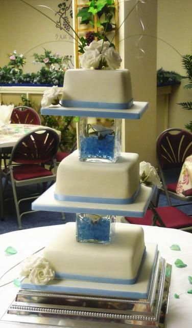Three tier square wedding cake with white roses topper and glass