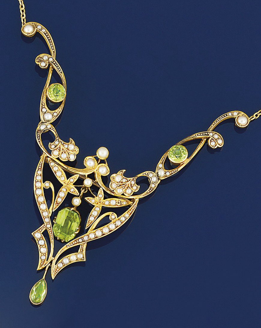 An Edwardian gold, peridot and half-pearl necklace  The central cut-cornered rectangular peridot suspended within a tapering scrolling foliate openwork panel with pear shaped peridot drop, to half-pearl scrolling shoulder panels with circular peridot detail, to a tracelink neckchain, circa 1905