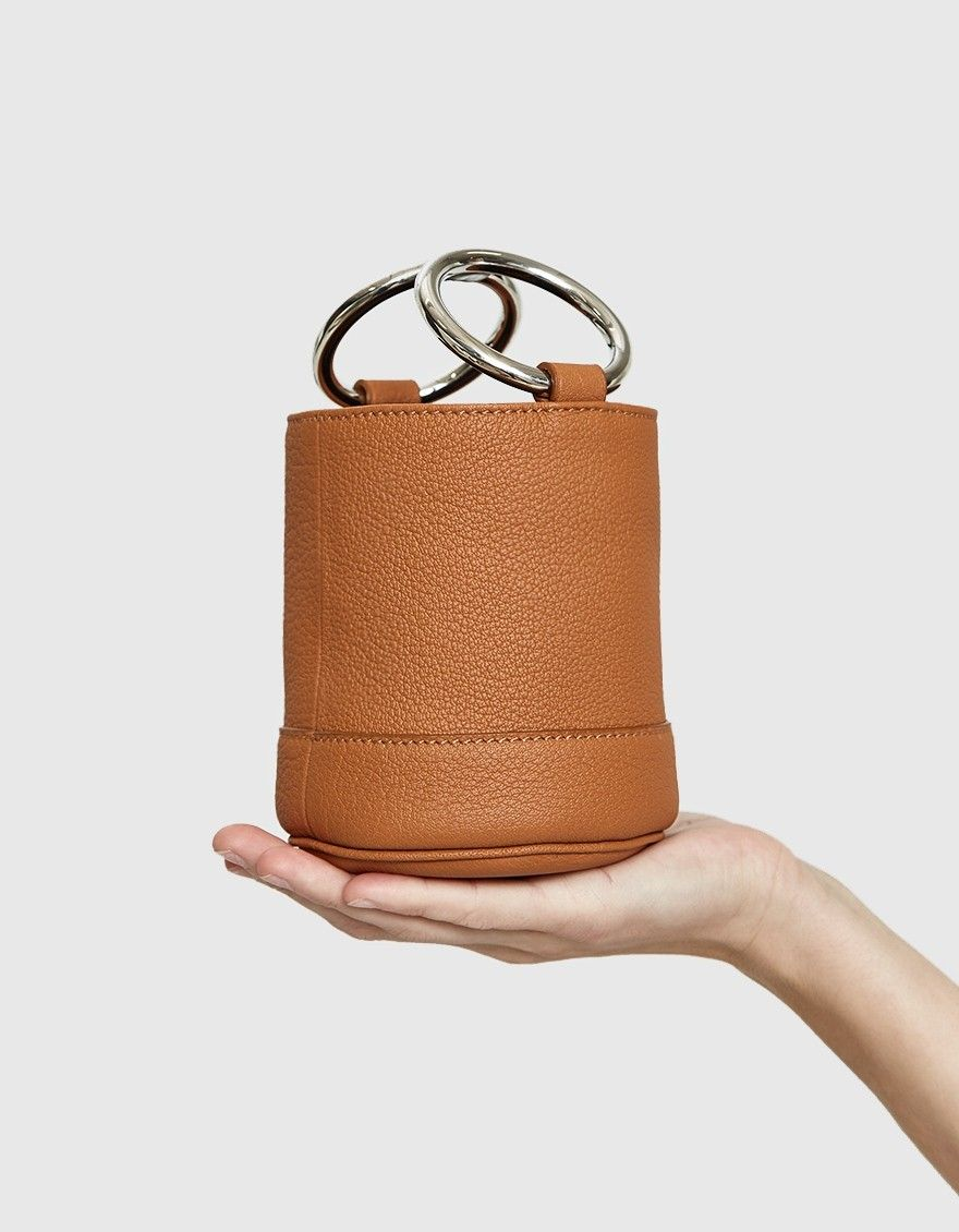543a0fcc8768 Mini bucket bag from Simon Miller in Tan. Pebbled leather. Structured base.  Cylindrical design. Two polished silver top handles. Tonal topstitching.