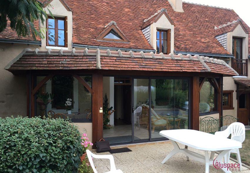 Véranda près de Bourges mixte aluminium et bois et acrotère en tuiles Une véranda dans laquelle ...