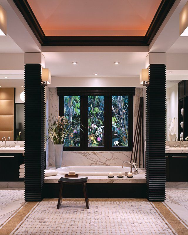 black & white modern bathroom. Columns around tub or shower separate his and hers vanities and toilets!