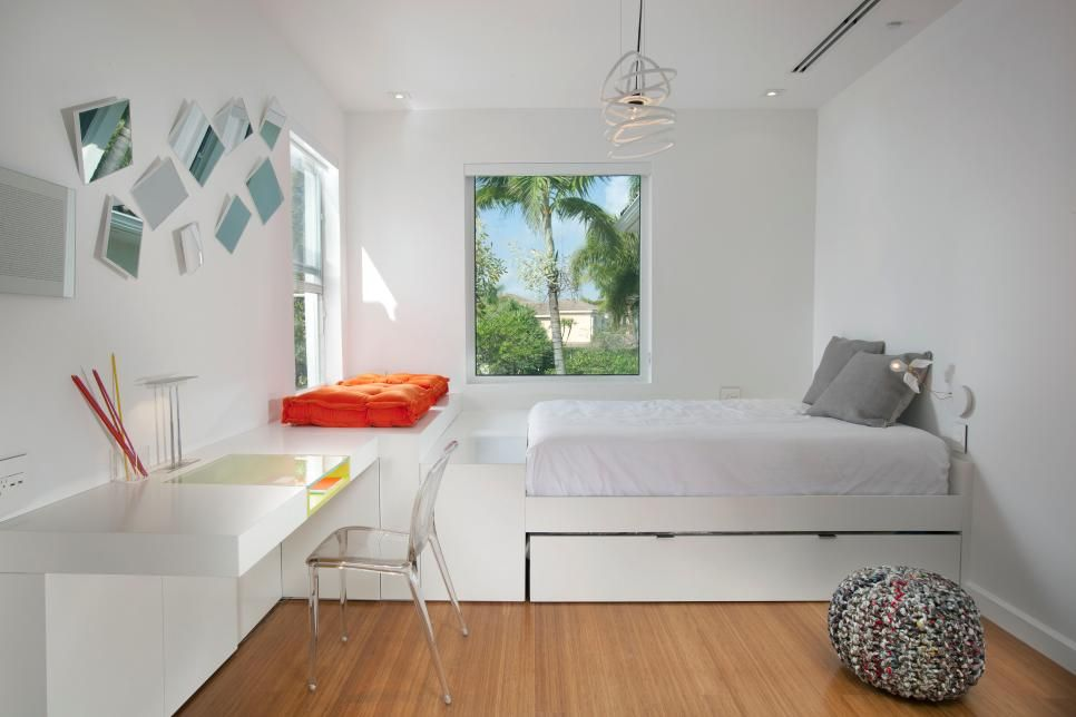 A Floating Desk And Acrylic Chair In This Bedroom Play Into The
