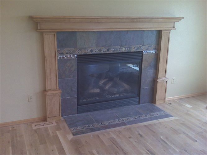 Oak fireplace mantel and surround. Slate tile around fireplace with inlay pattern and glass tile.  Idea for our fireplace tile?