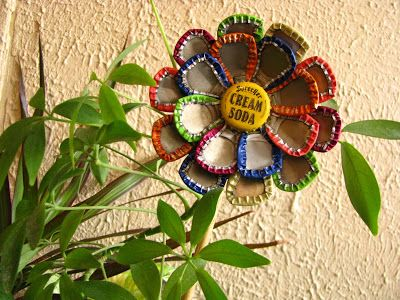 DIY Bottle Cap Flower Garden Art Stake It takes a little trial an error but all you do is take heavy duty pliers and smash the bottle caps into petal shapes and then epoxy or use a super glue rated for metal and attach to a can top in at least two circular rows. Then glue a stick to the back after it's dried 24 hrs. Easy once you get the hang of smashing bottle caps :)
