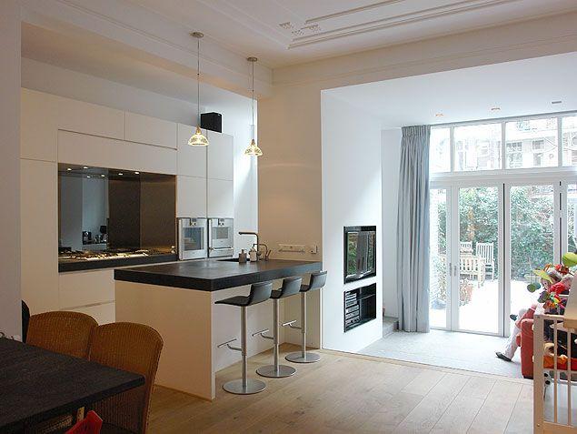 Strakke keuken met kooknis en keukeneiland in woning amsterdam oud