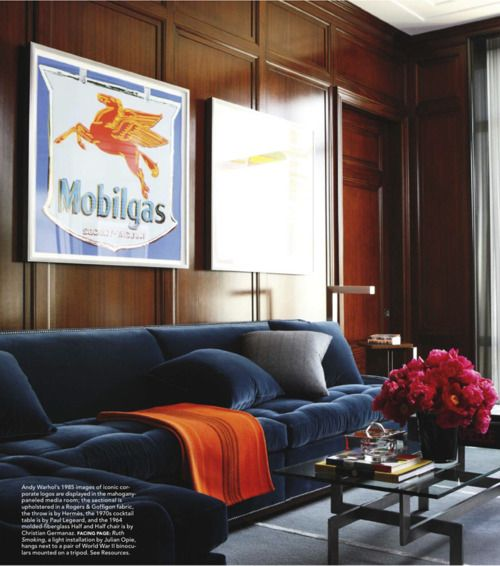 The mix of the wood paneling with the modern table and the blue velvet sofa is so nice.  The punches of orange and pink are perfect.