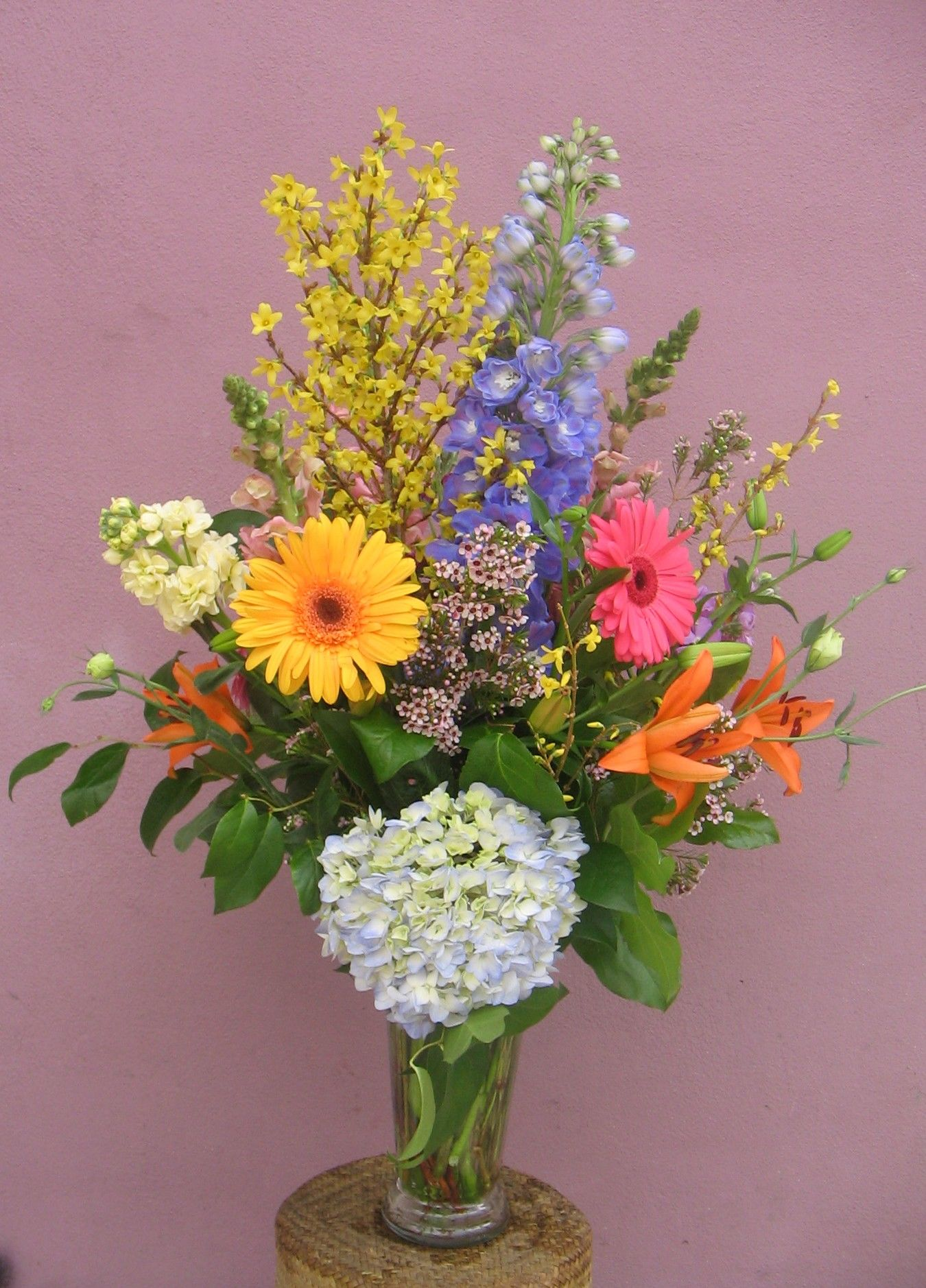 100-2 100.00 Classic WOW! This wonderful arrangement combines late spring and early summer blooms. The flowering forsythia branches add a sentiment of renewal, offset by the calming blues of the hybrid delphinium and softest blue hydrangea. We've added gerbera daisies and hot orange lilies for eye-popping excitement. A truly wonderful assortment.
