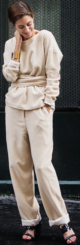 Camel sweater wrapped at waist, gold cuff, cuffed pants, and black sandals