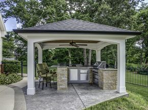 This Impressive Outdoor Cooking Area Features A Hip Roof With Arches Over Decorative Concrete Patio The Ceiling Is Stained Wood Fan