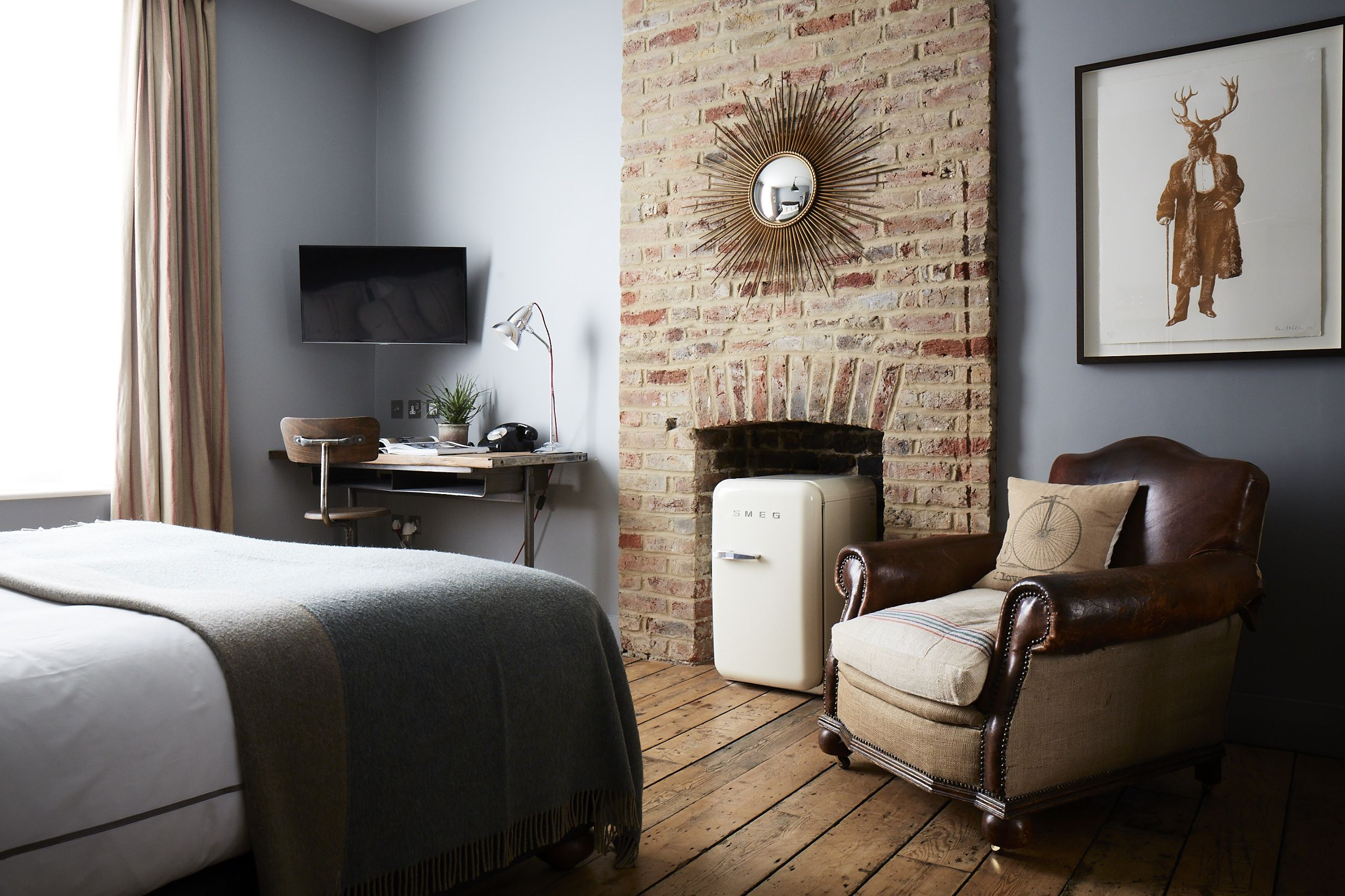 Medium room at artist residence london featuring a vintage leather club chair white smeg mini