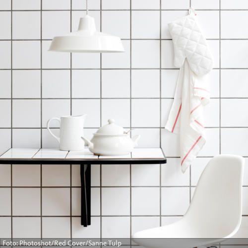 Quadratische, weiße Fliesen an der Wand erstrecken sich über die ...