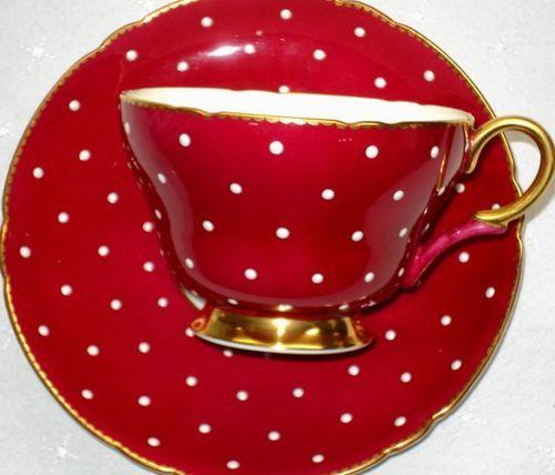 Arrume a mesa para o chá: Toalha branca de linho , coloque as porcelanas vermelha com bolas branca com filete dourado.