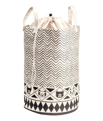 Naturhvit/Tiger. En sylinderformet oppbevaringskurv i stødig bomullstwill med trykt mønster. Den har to hanker øverst. Plastet innside. Diameter 34 cm,