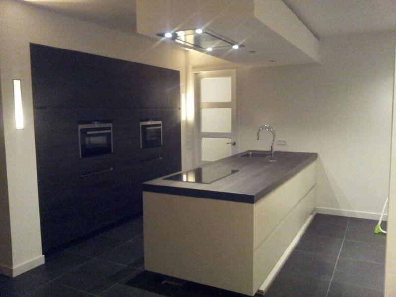 Kasten wand eikenkleurig zwart met spoelkookeiland in kristal met hoge kraan en dik werkblad - Beeld van eigentijdse keuken ...
