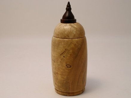 Elm Treen bottle with Bois de Rose minaret finial. The finial is made from a rare wood from Madagascar, a member of the rosewood family. While being shaped on the lathe it smells of cinnamon and honey. The dark discolorations and the white splotching on the left of the photo is called spalt, and is essential the process of fungal rot that has been stopped before the wood has lost structural integrity. Much desired by wood artisans.