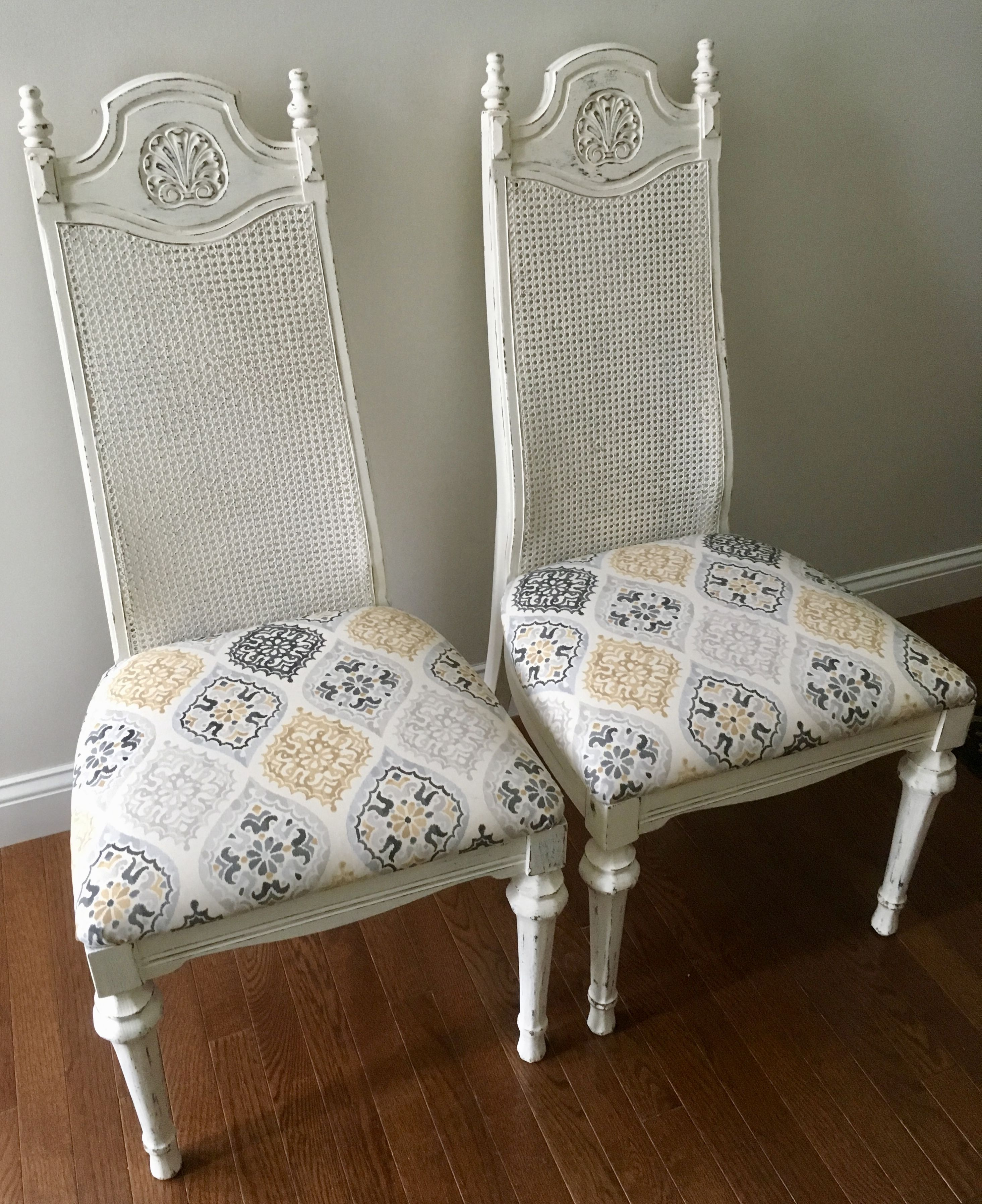 Pair of painted and distressed cane back chairs with updated upholstery