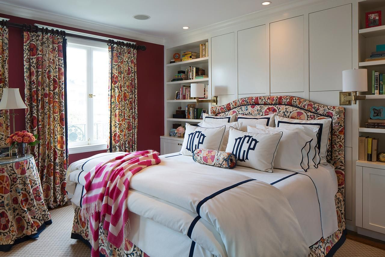 Simple blue and white bedding crisply contrasts with the vibrant floral curtains and upholstered bed frame in this traditional bedroom. Built-in floor-to-ceiling shelves and cabinets frame the bed and provide lots of storage and display space.