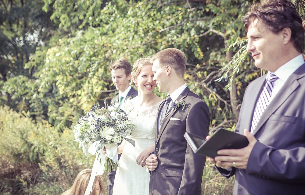 Bride and groom in outdoor wedding ceremony - photo by New Vintage Media