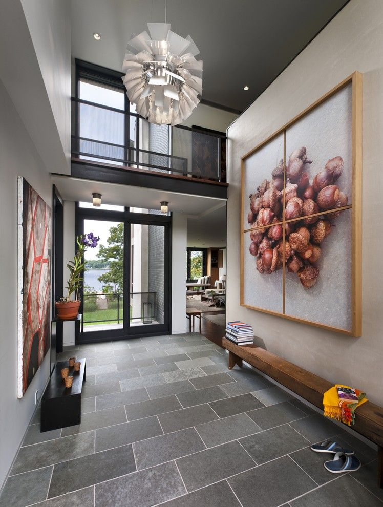 Modern gray entryway with fun lighting glass front door and loft large scale art