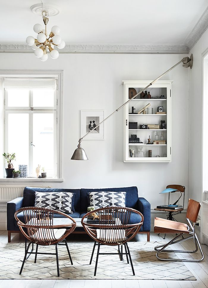 a cozy living room with white walls, industrial modern lighting, and