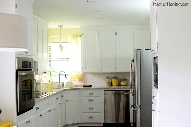 White Kitchen - painted the extisting stained cabinets and added new nickel hardware. New granite counter, subway tile backsplash and appliances. LOVE a white kitchen!!