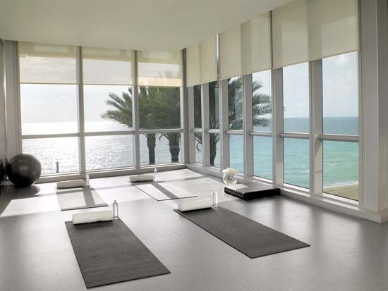 Relaxing Yoga Room Of Jade Ocean House Surrounded By Glass Windows Covered  By Shade And Completed With Mats