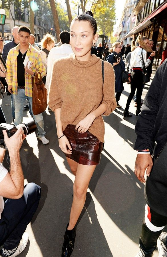 Bella Hadid wears a camel sweater, leather miniskirt and boots
