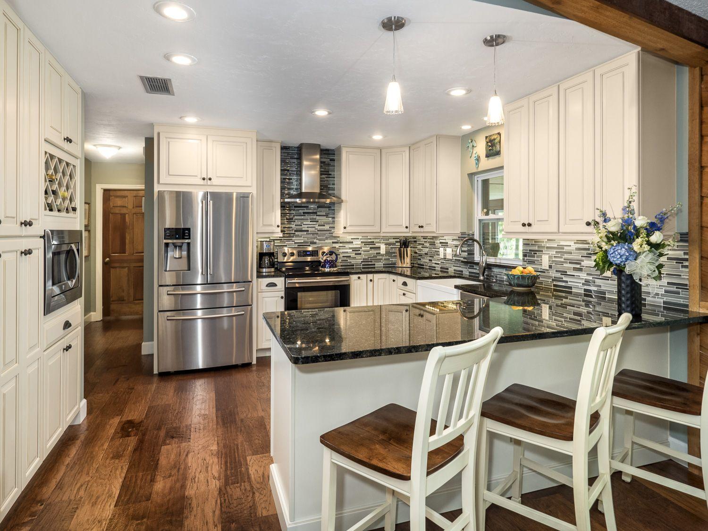 Cream Colored Cabinetry, wood floors, dark granite ...