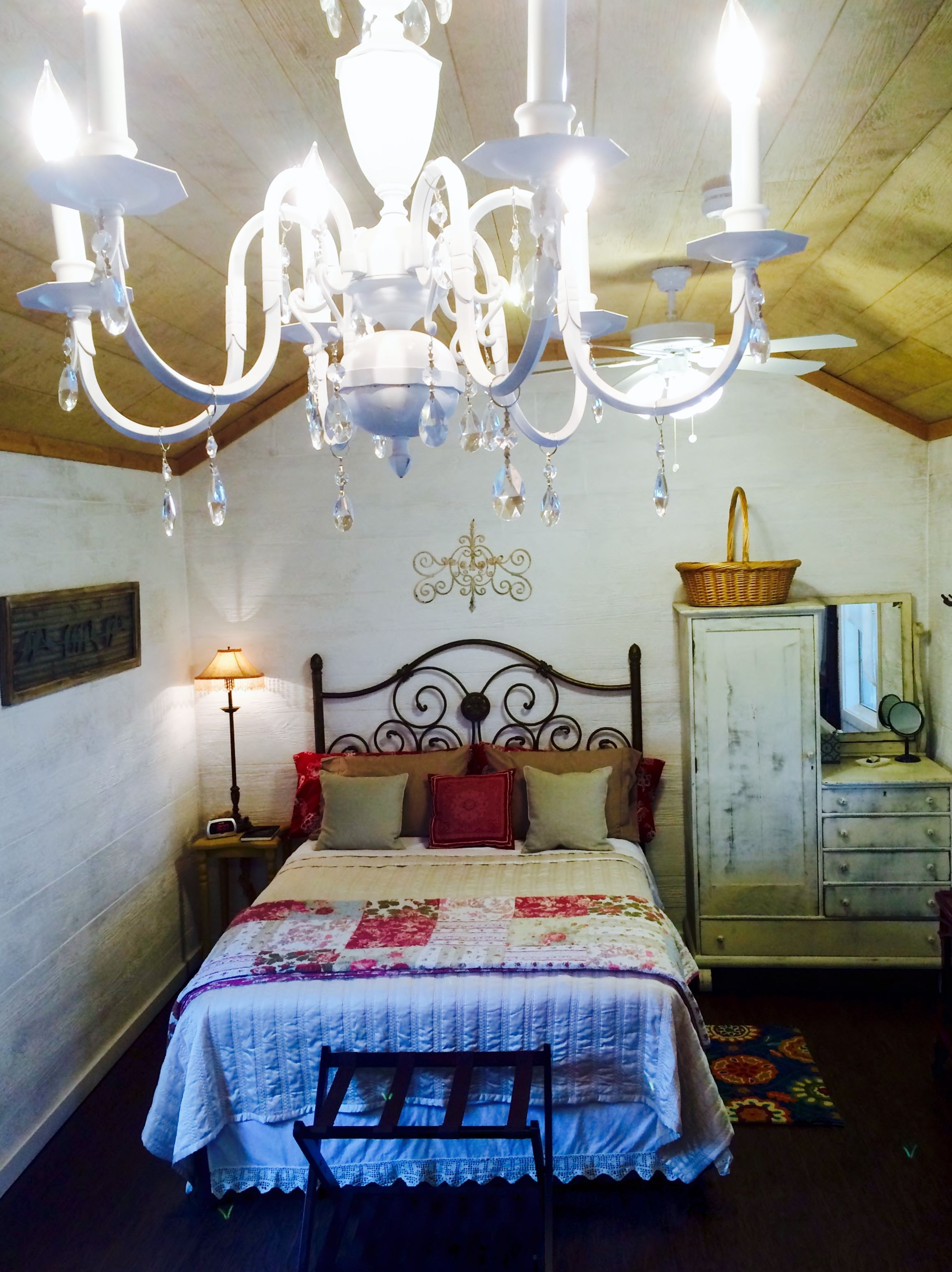 A vintage chandelier lights up this elegant little cottage with queen bed and antique chiffarobe.