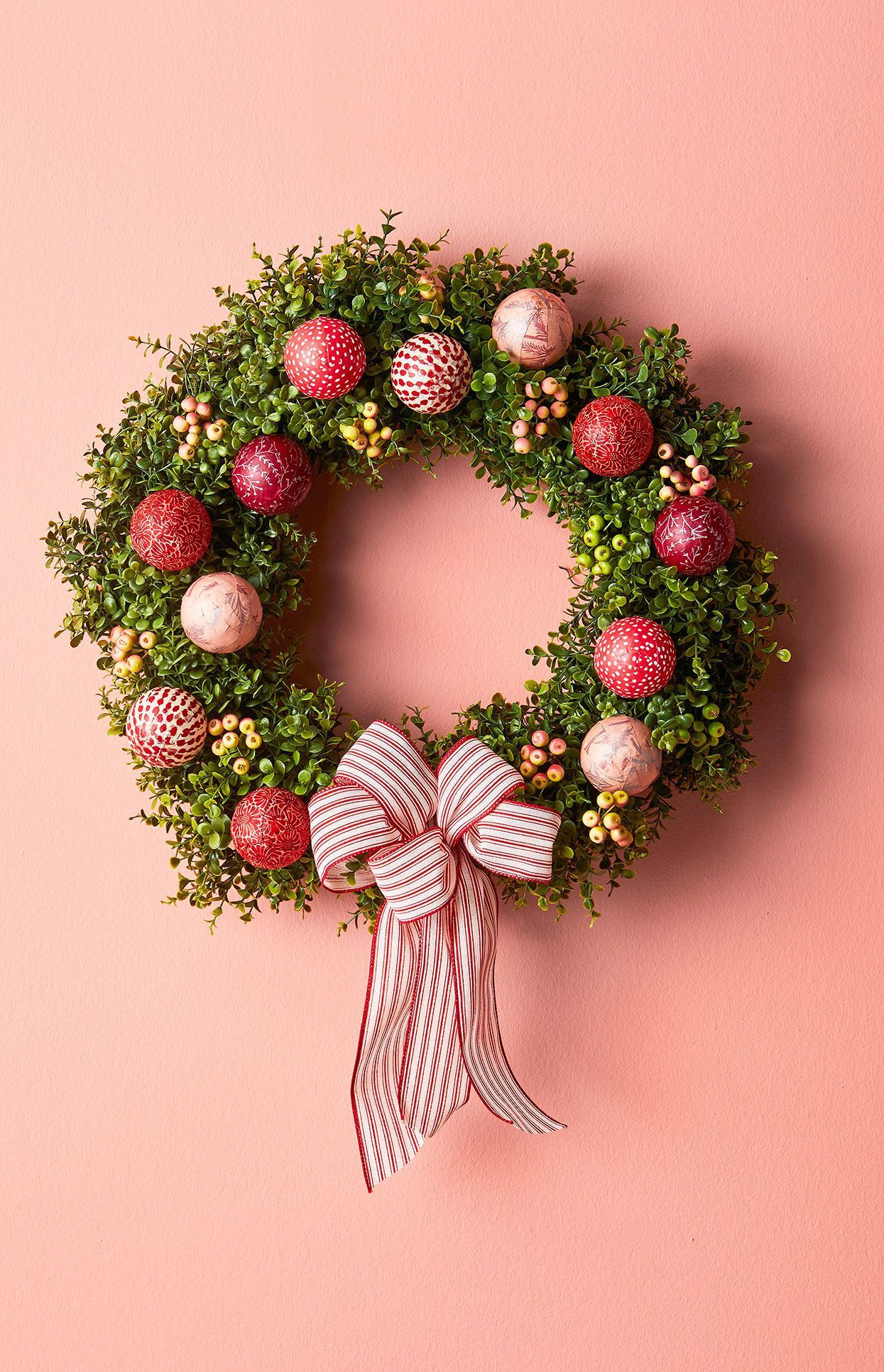 Crafting these decoupaged Christmas ornaments is the perfect project to use up that stash of scraps from old rolls of wrapping paper. A candy-striped pom-pom bow is a finishing touch for this pretty-as-a-present faux boxwood wreath. #christmas #holidaydecor #wreath #holidaywreathideas #diychristmaswreath #bhg