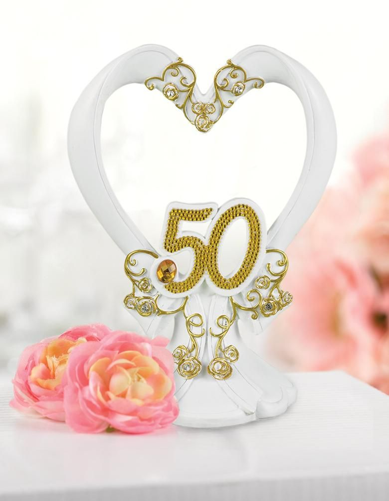 "Gilded 50th Wedding Anniversary Cake Topper made of white resin. It is in a romantic heart shape with a round base. The base is carved with a scalloped bottom and a bow detail. Rising from the bow is the heart with a carved curved shape. There are also carved filigree accents that are painted gold. Sitting at the base of the heart is a rhinestone studded ""50"" emblem with a amber rhinestone accent."