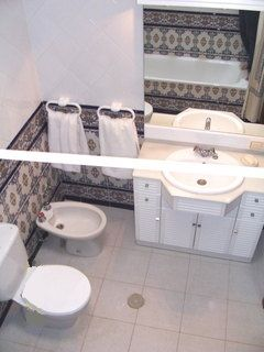 The bathroom, with Andalusian tiles, and reflected in the mirror, the tub