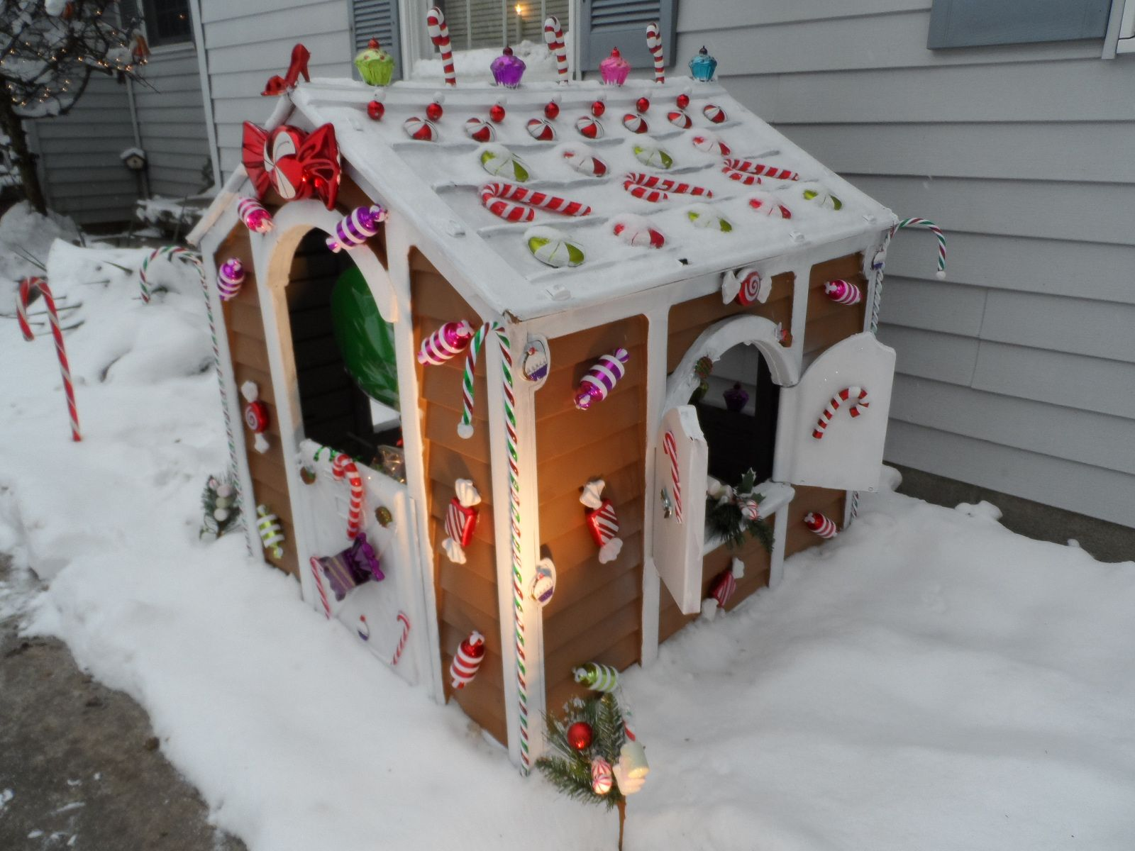 Gingerbread house created from my son's old playhouse.  Used some brown and white paint and hot glued the candy ornaments on it.