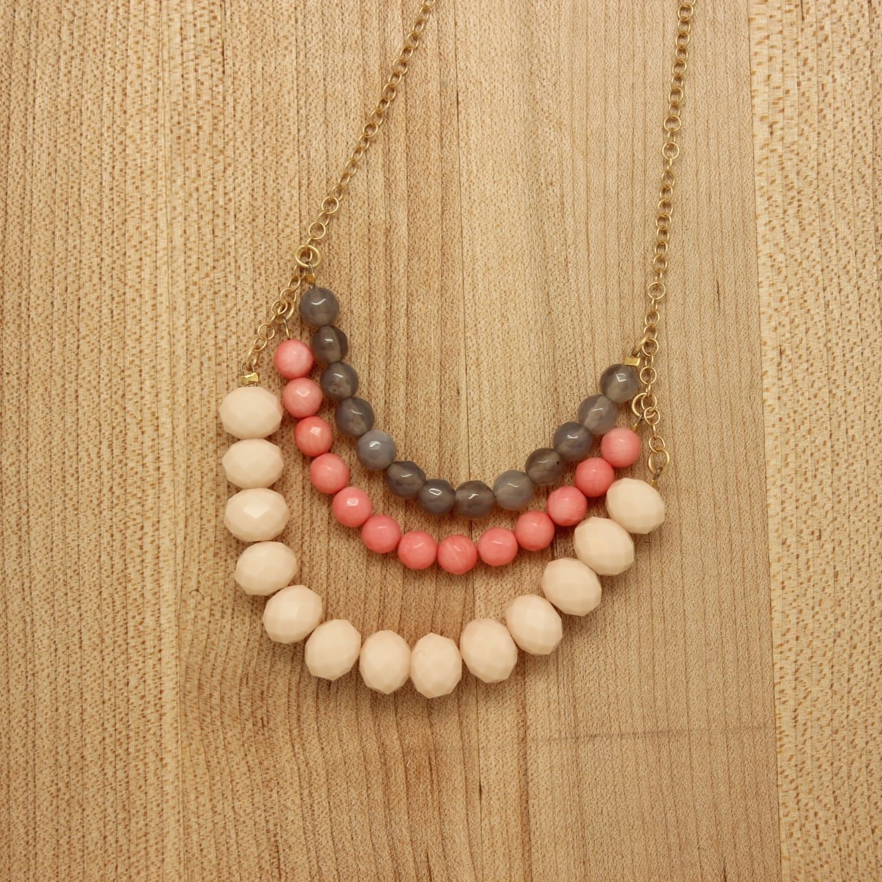 Gray agate, coral and pale pink glass three stranded necklace. Gold plate over brass chain, measuring 18″ with a 2″ extender chain. Handmade in Portland, Oregon.