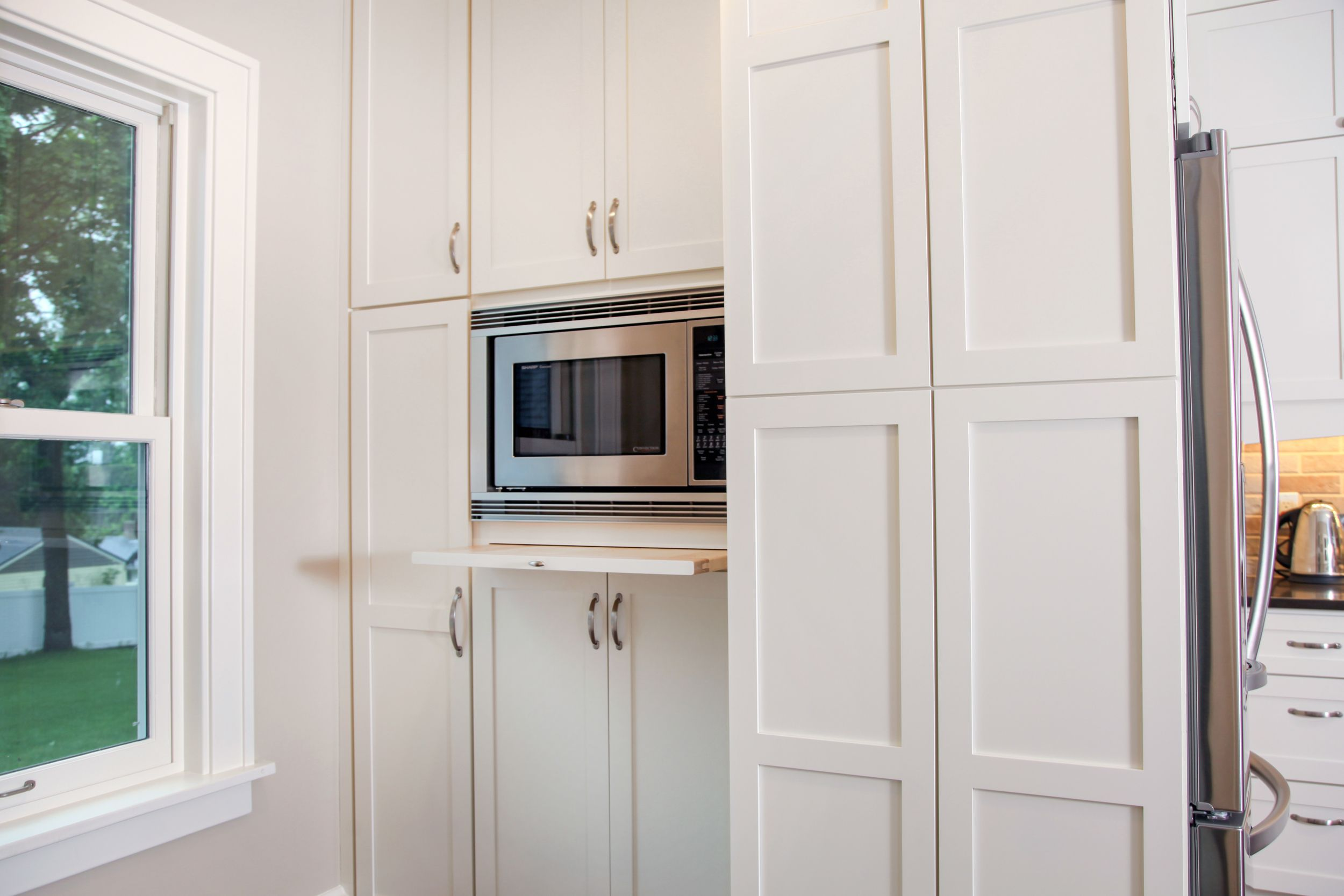 Pantry storage with microwave and pullout cutting board ...