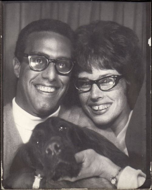 1960s couple wearing glasses and with their Irish setter dog in a Photo booth. How about that Tooth gap