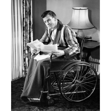 Mature man sitting in a wheelchair and reading documents Canvas Art - (18 x 24)